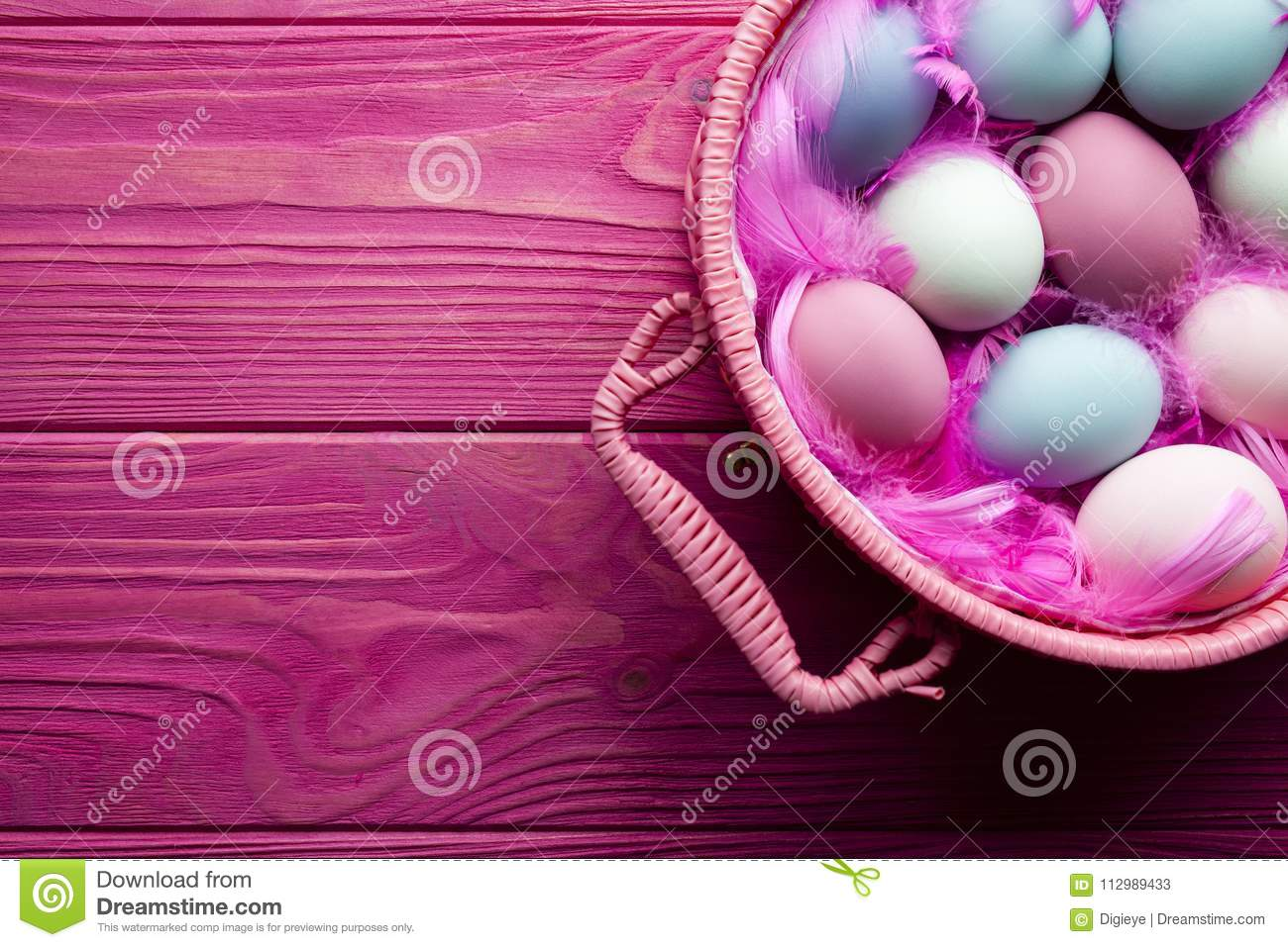 Colored Easter eggs and feathers in basket on pink background