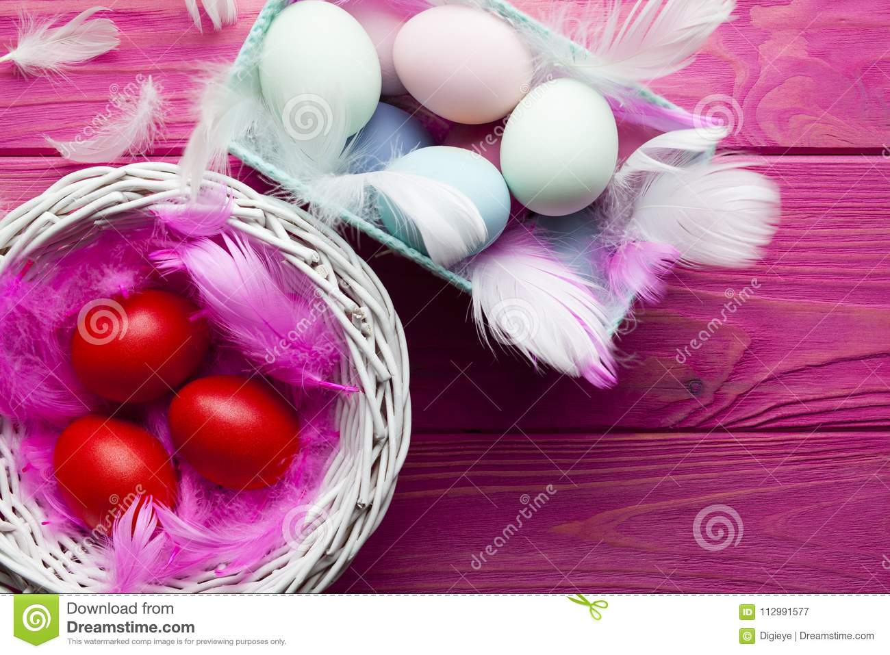 Colored Easter eggs, feathers and baskets on pink background