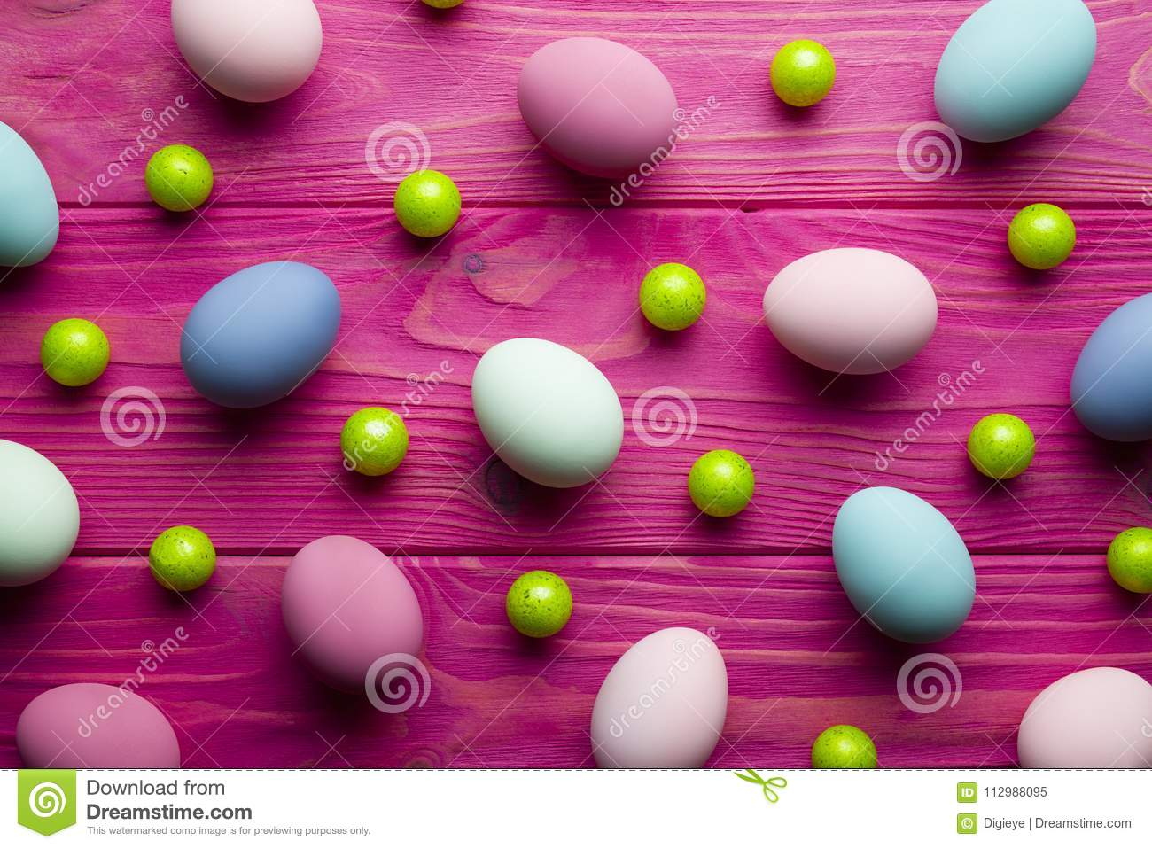 Colored Easter eggs and green balls on wooden background