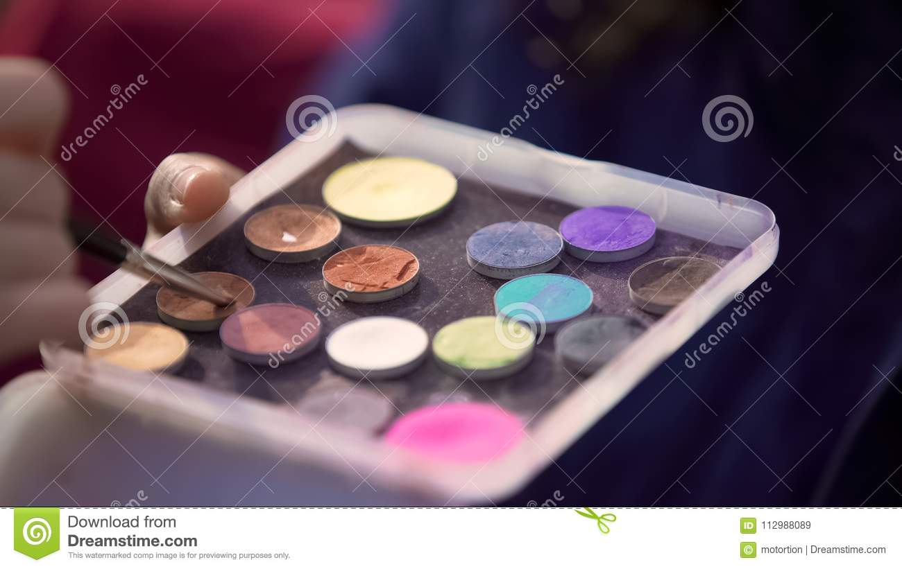 Colored eyeshadows palette close-up view, makeup artist working, beauty fashion