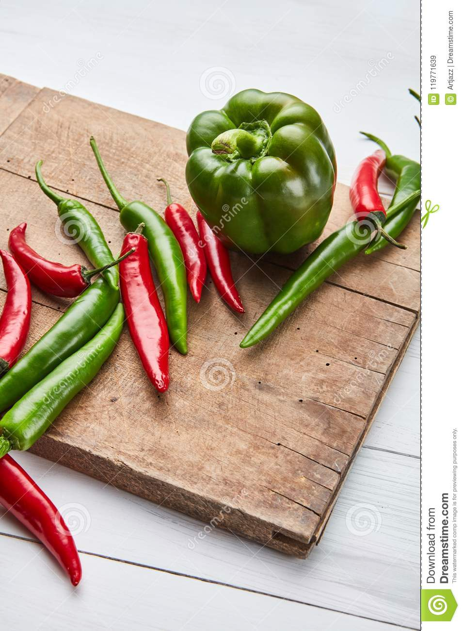 Colored hot chili peppers on a wooden board