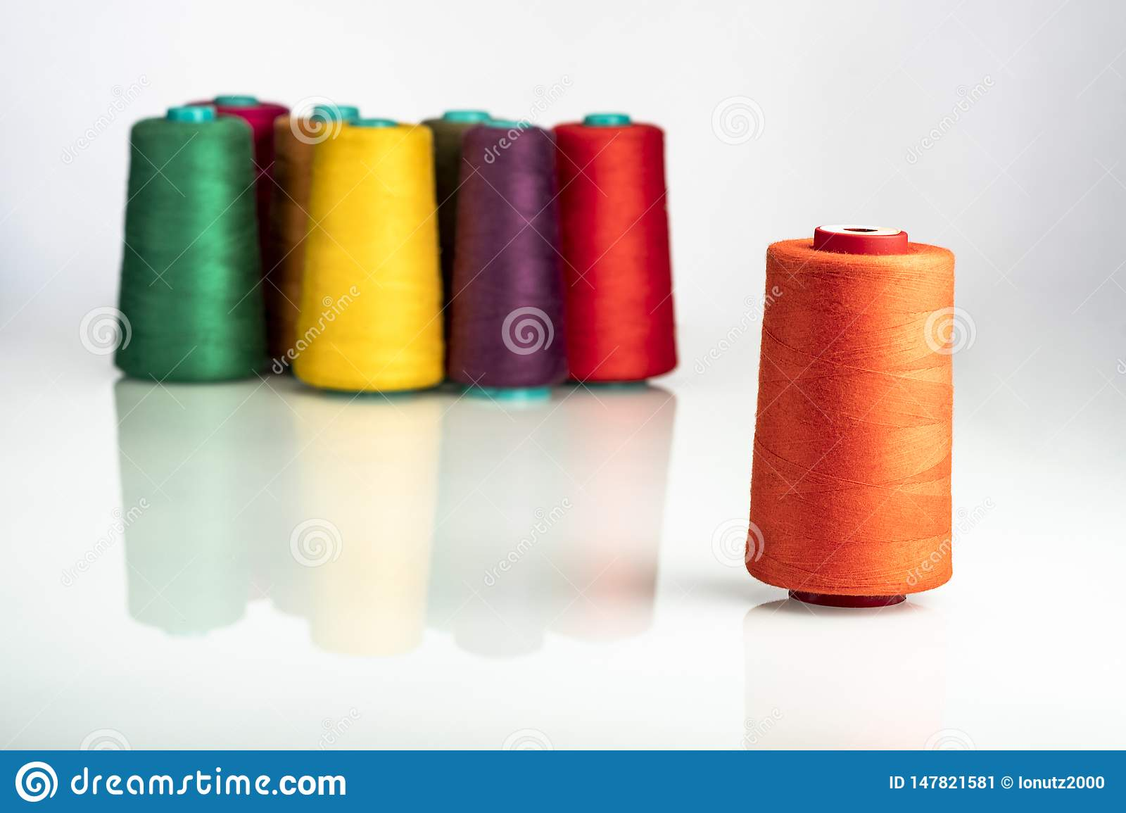 Colored industrial spools arranged on white background
