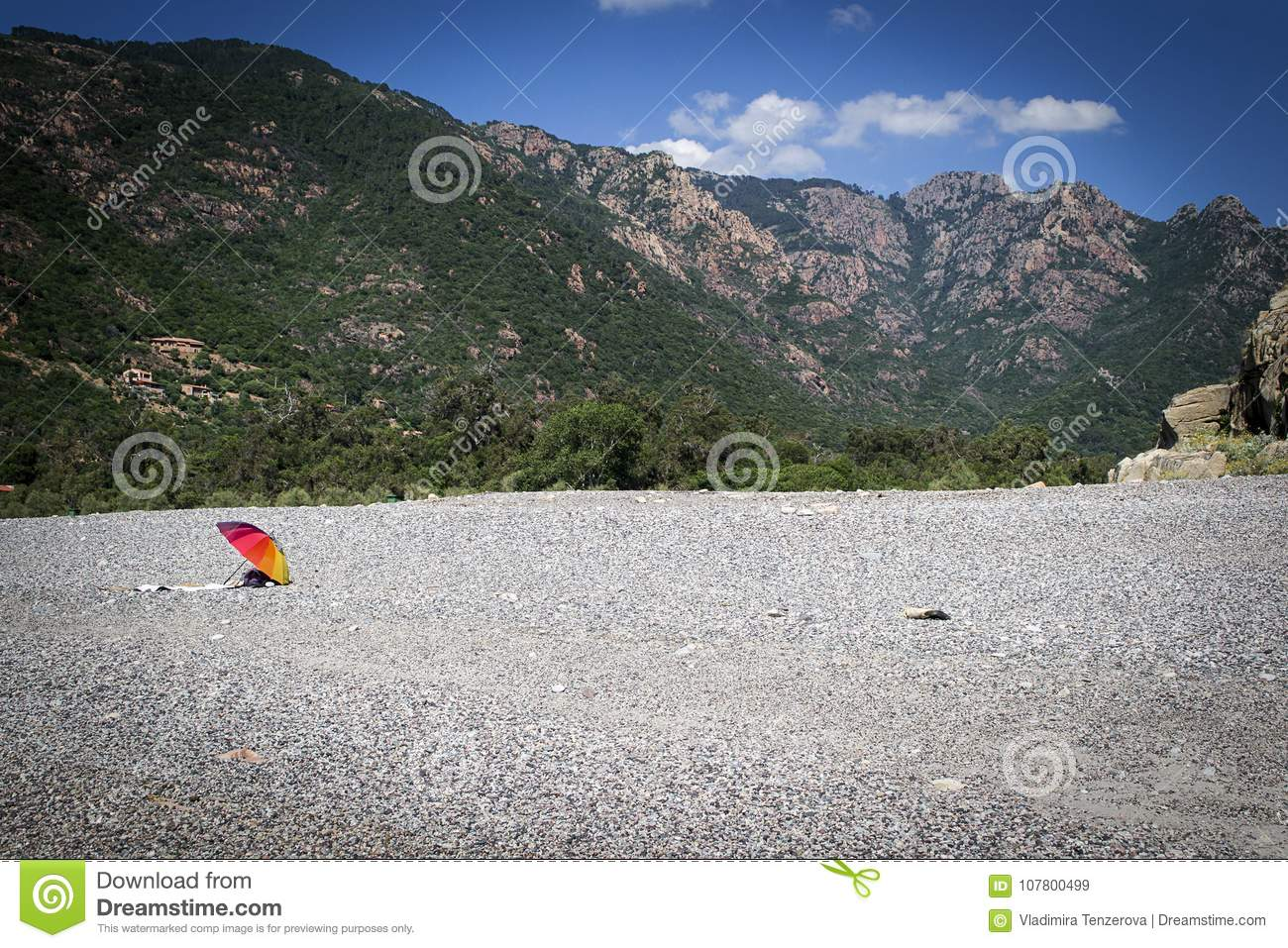 The only colored parasol on an empty beach between the mountains on the  coast of the island of Corsica f64255dcbe2