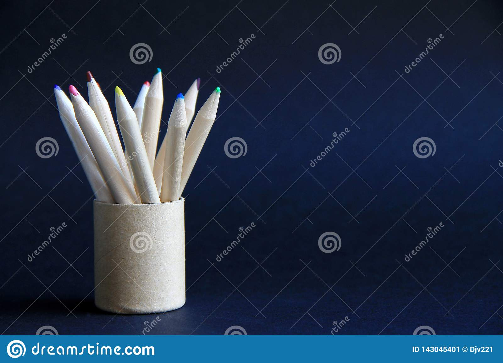 Colored pencils in a round cardboard box on a dark background