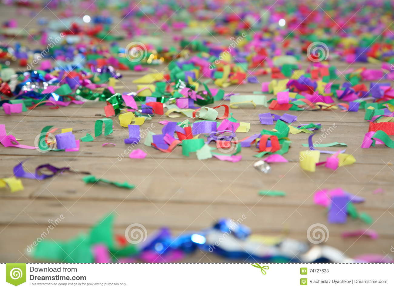 Colored streamers confetti scattered on the wooden plank floor. Happy party background.