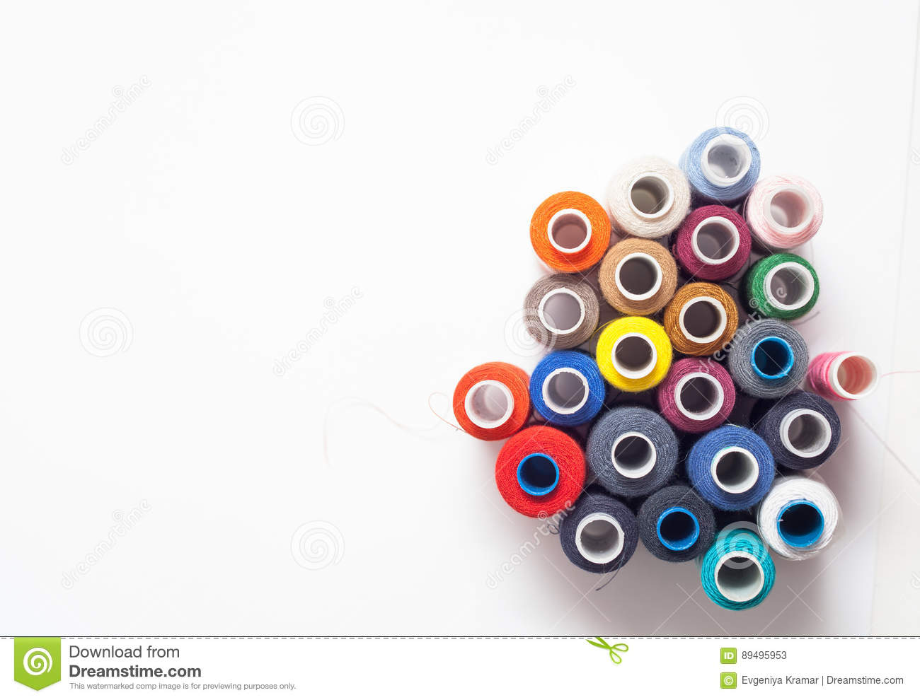 Colored thread coils on white background, sewing tools