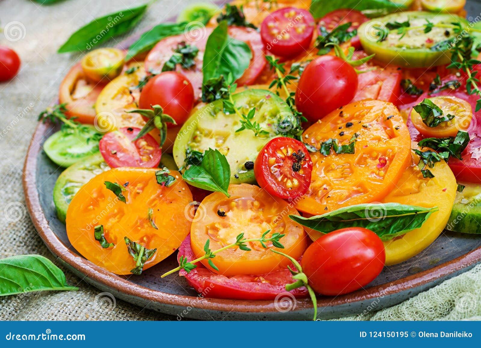 Colored tomato salad with onion and basil. Vegan food.