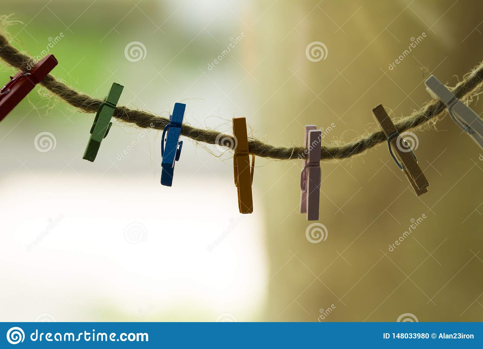 Colored wooden clothespins hanging on a wire
