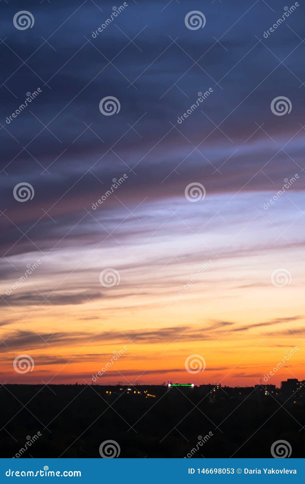 Colores azul-anaranjados del cielo de la puesta del sol con las nubes dramáticas
