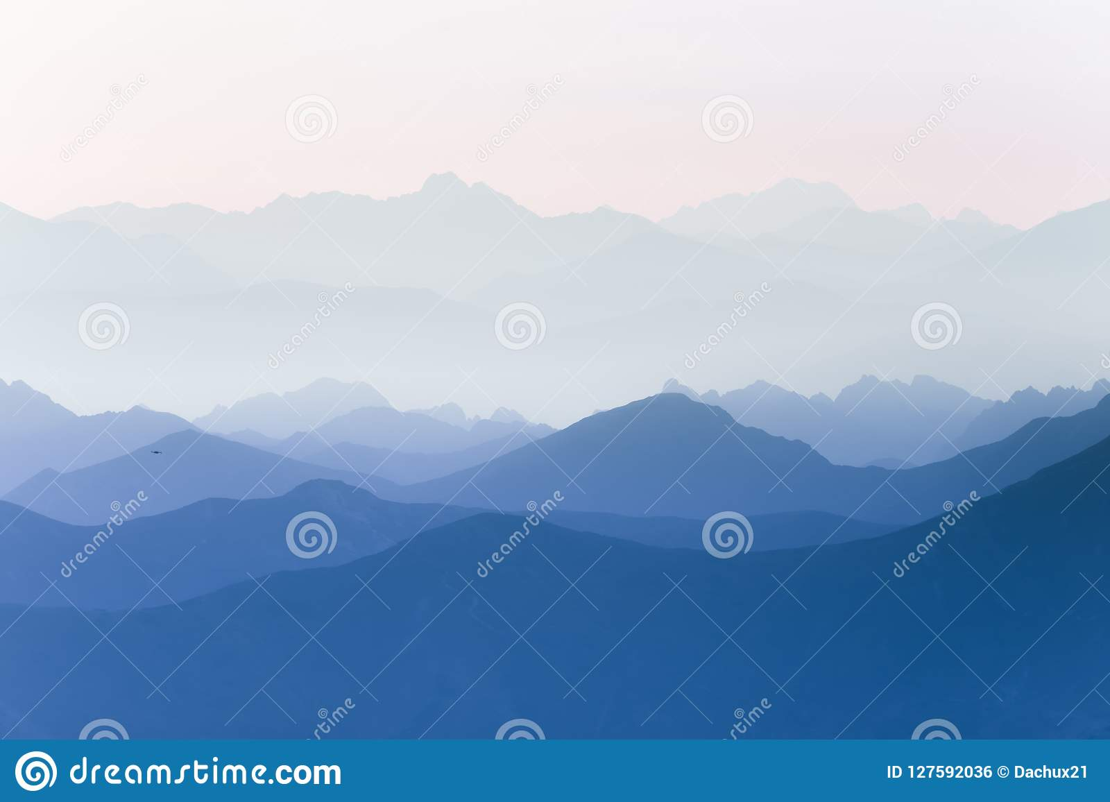 Colorful, abstract double exposure of mountains in sunrise. Minimalist scenery with color gradients.