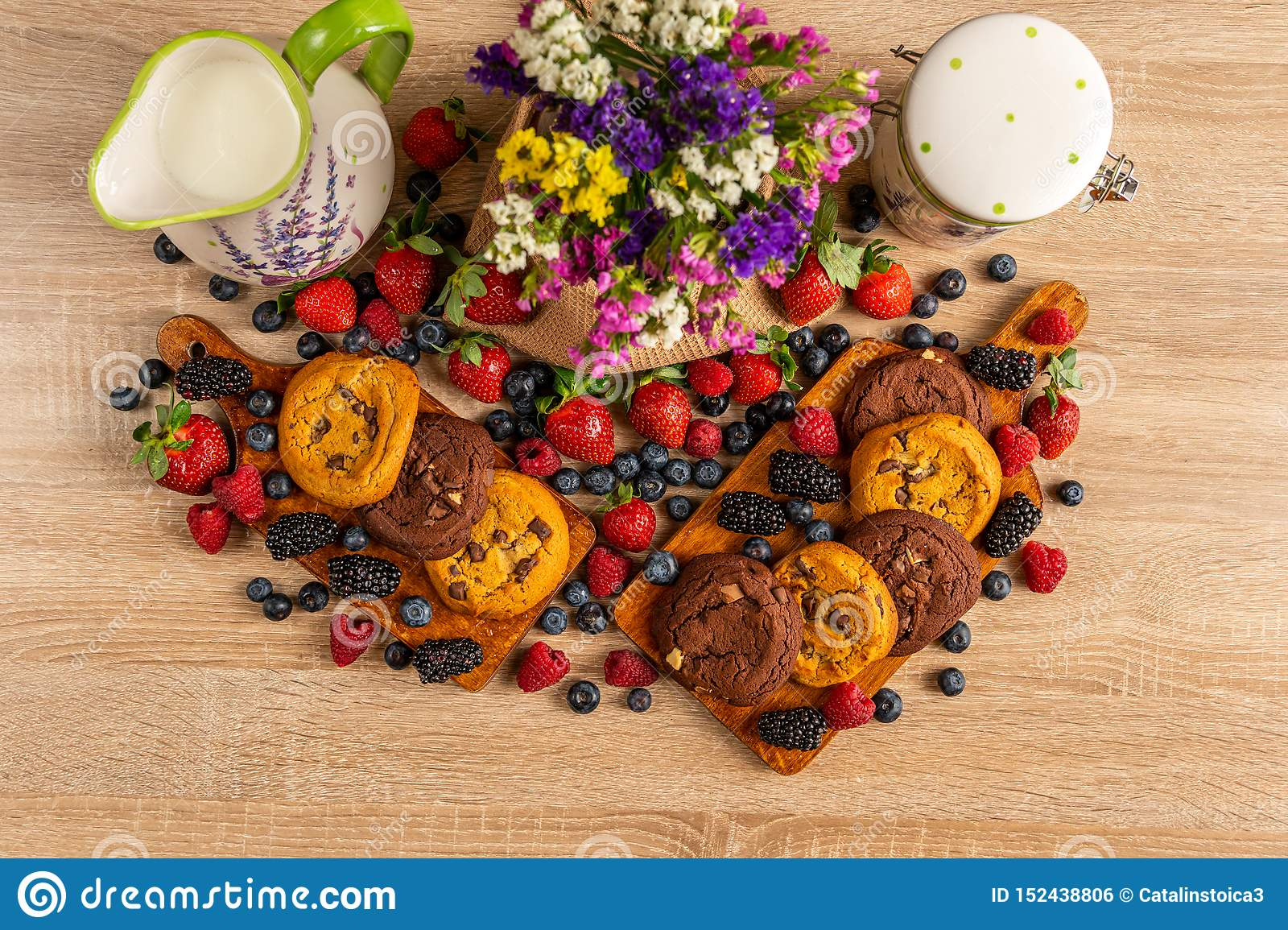 Colorful assorted mix of wild berries, brown cookies, milk and flowers