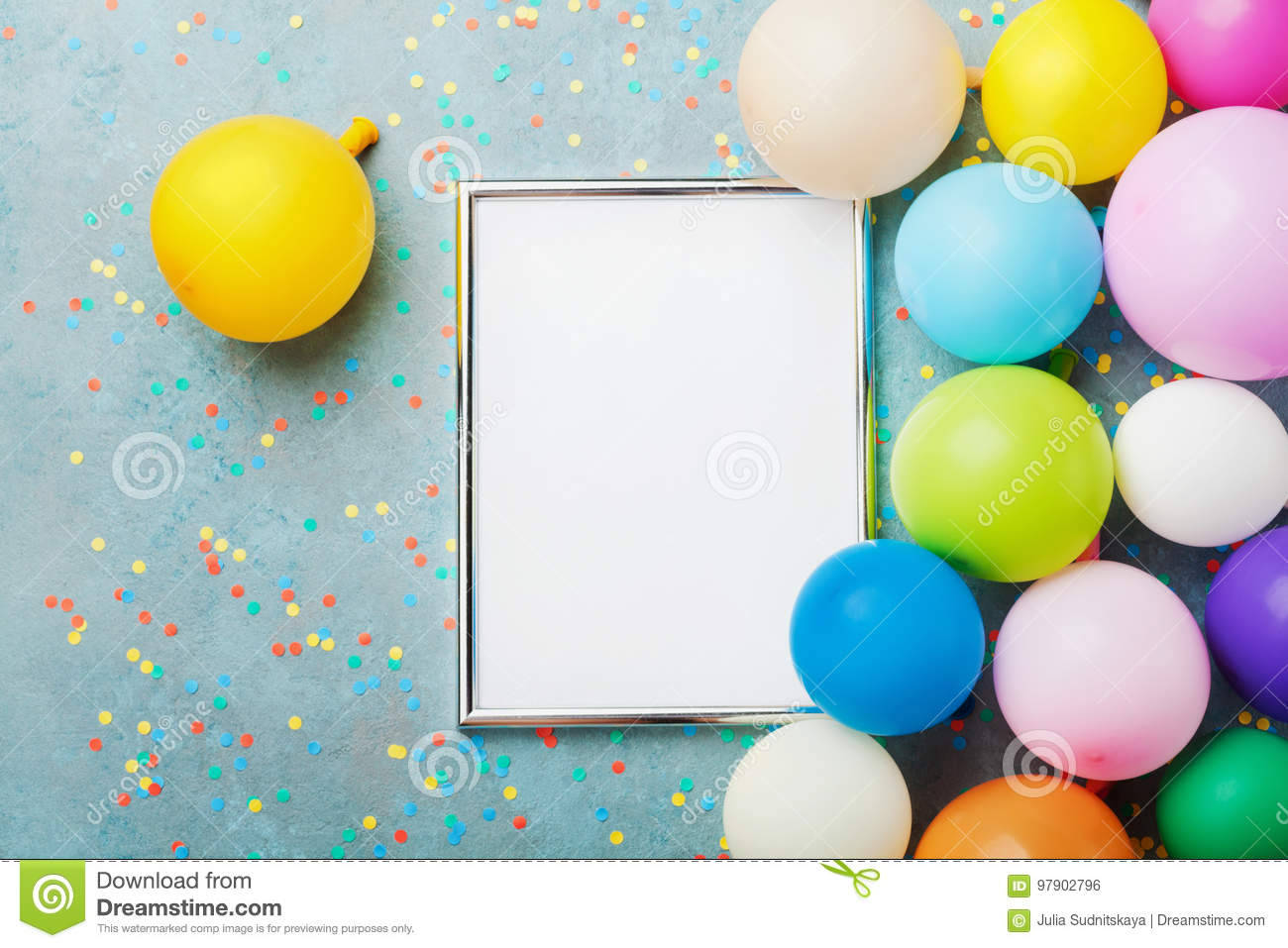 Colorful balloons, silver frame and confetti on blue table top view. Birthday or party mockup for planning. Flat lay style.