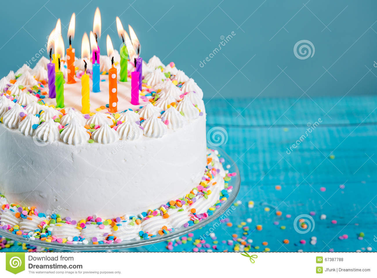 White Buttercream Icing Birthday Cake With Colorful Sprinkles And Candles Over Blue Background