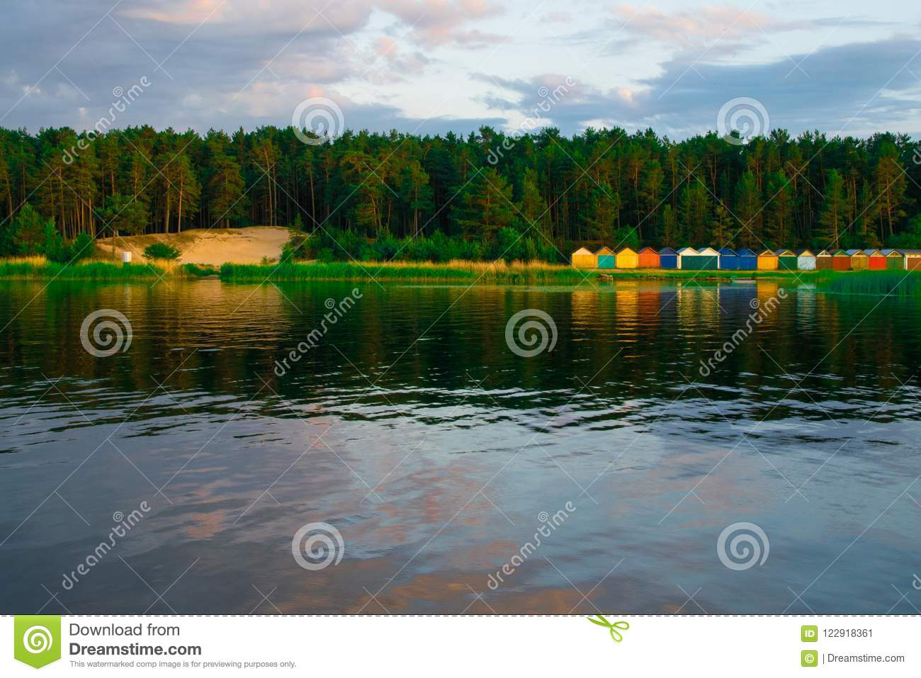 Colorful boat house on the edge of the water. Bright orange and green building is a waterside garage for boats.