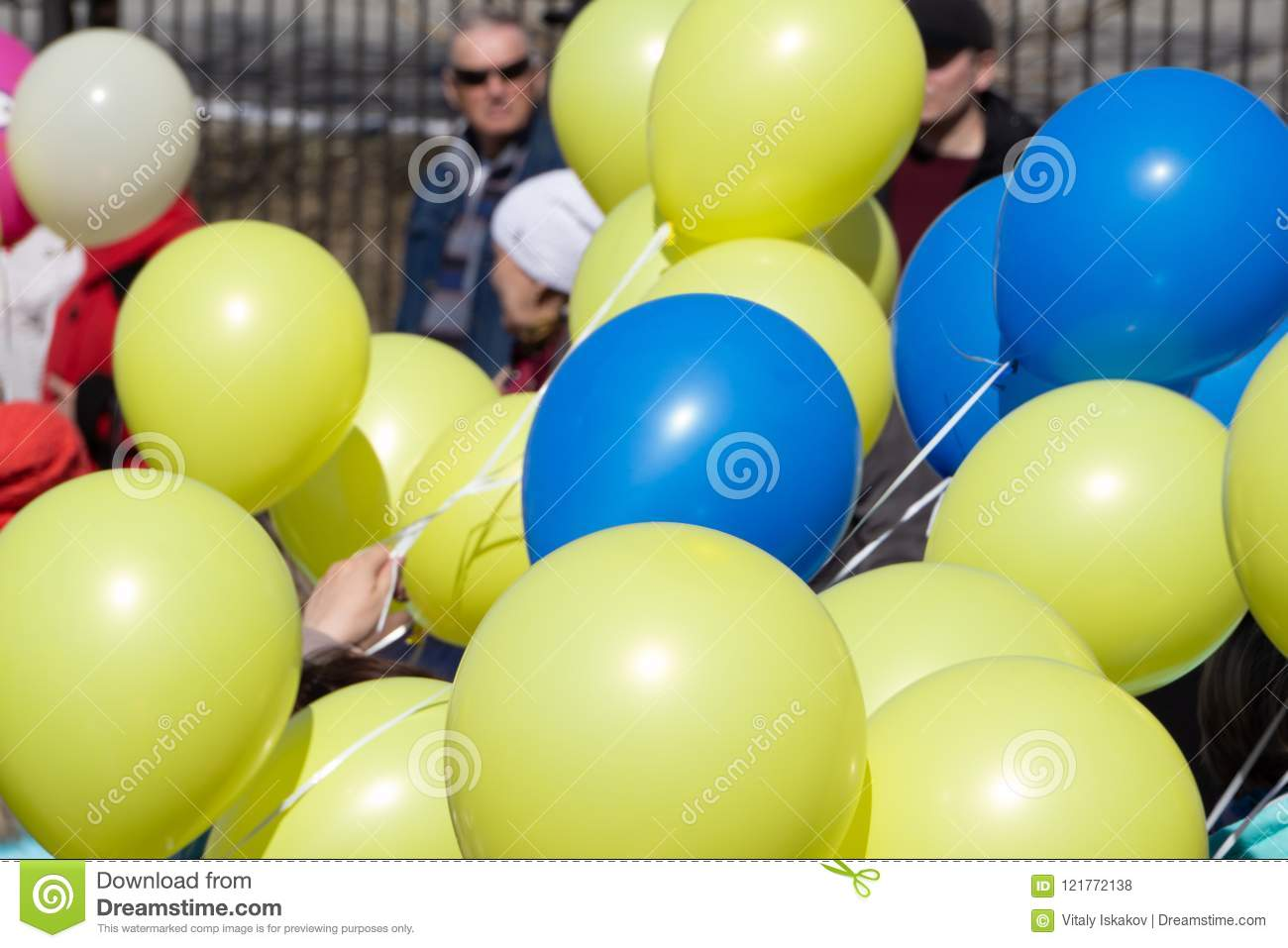 Colorful bouncing balls outdoors against blue sunny sky .