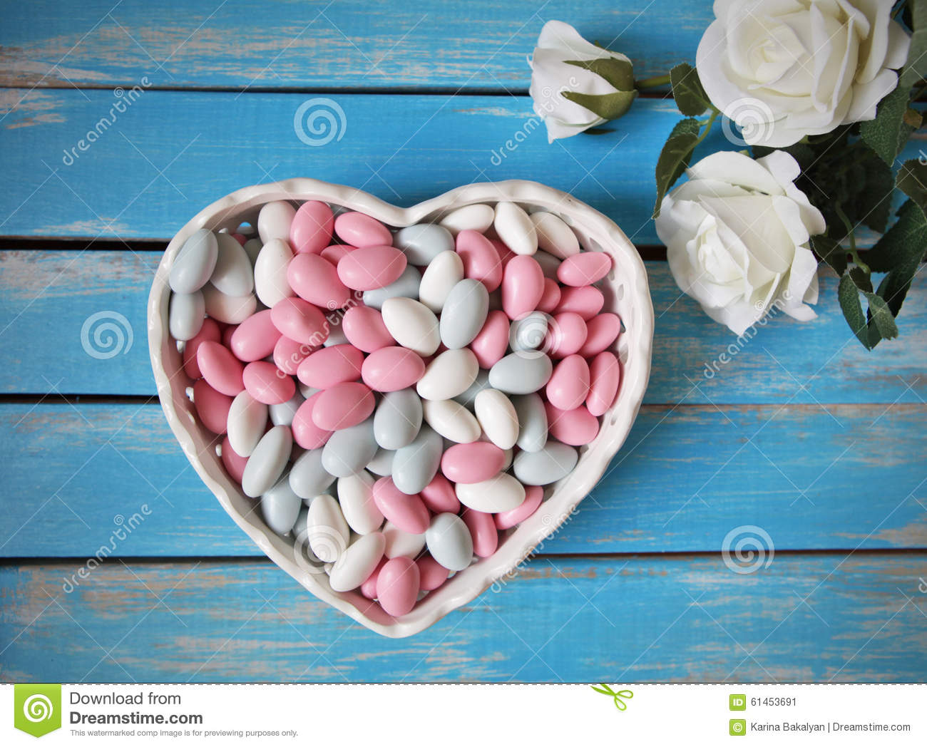Colorful candy in white heart shaped bowl and white roses on wooden table