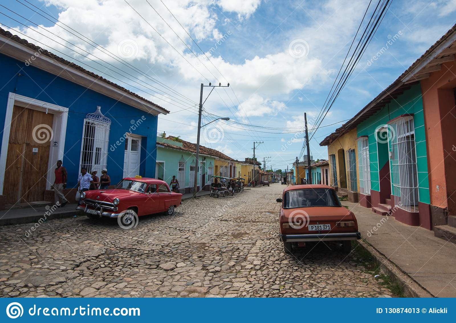 Colorful Caribbean aged village with cobblestone street, classic red car and Colonial house, Trinidad, Cuba, America.