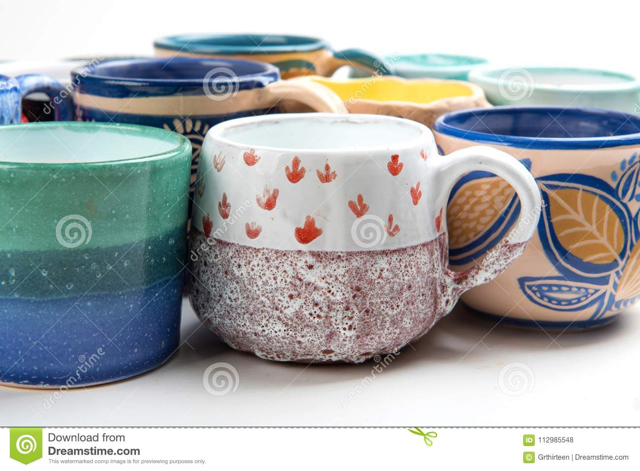 Colorful ceramic glazed cups on white background