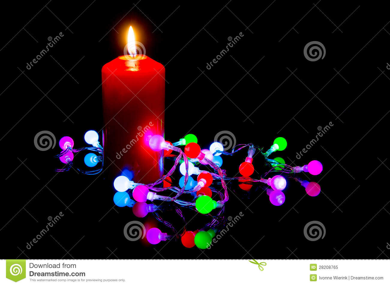 Colorful christmas lights with reflection and burning candle on back