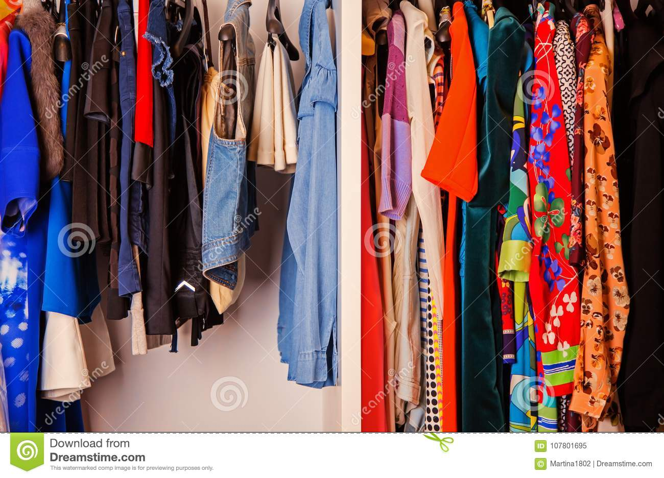 Colorful collection of female clothes hanging on a rack
