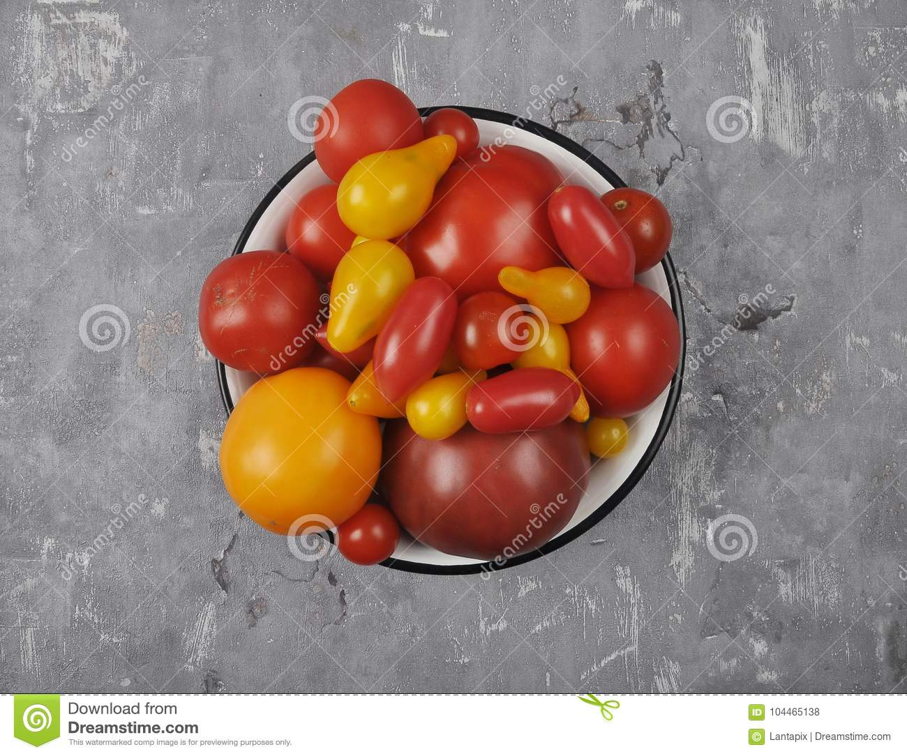 Variety of tomato cultivars in enamel bowl on concrete