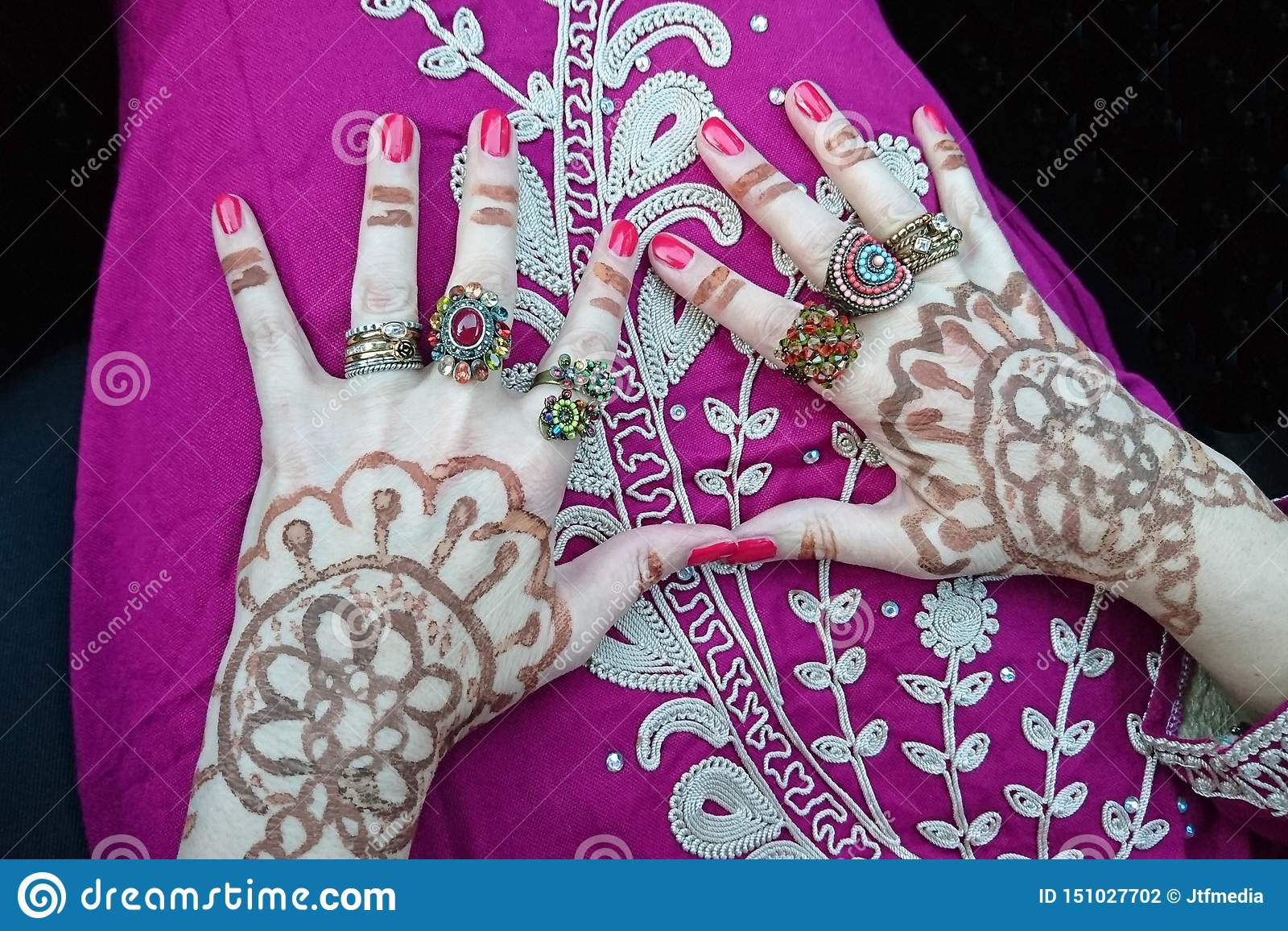 Wedding preparations: With henna and rings decorated hands on the lap of a woman in a Moroccan dress