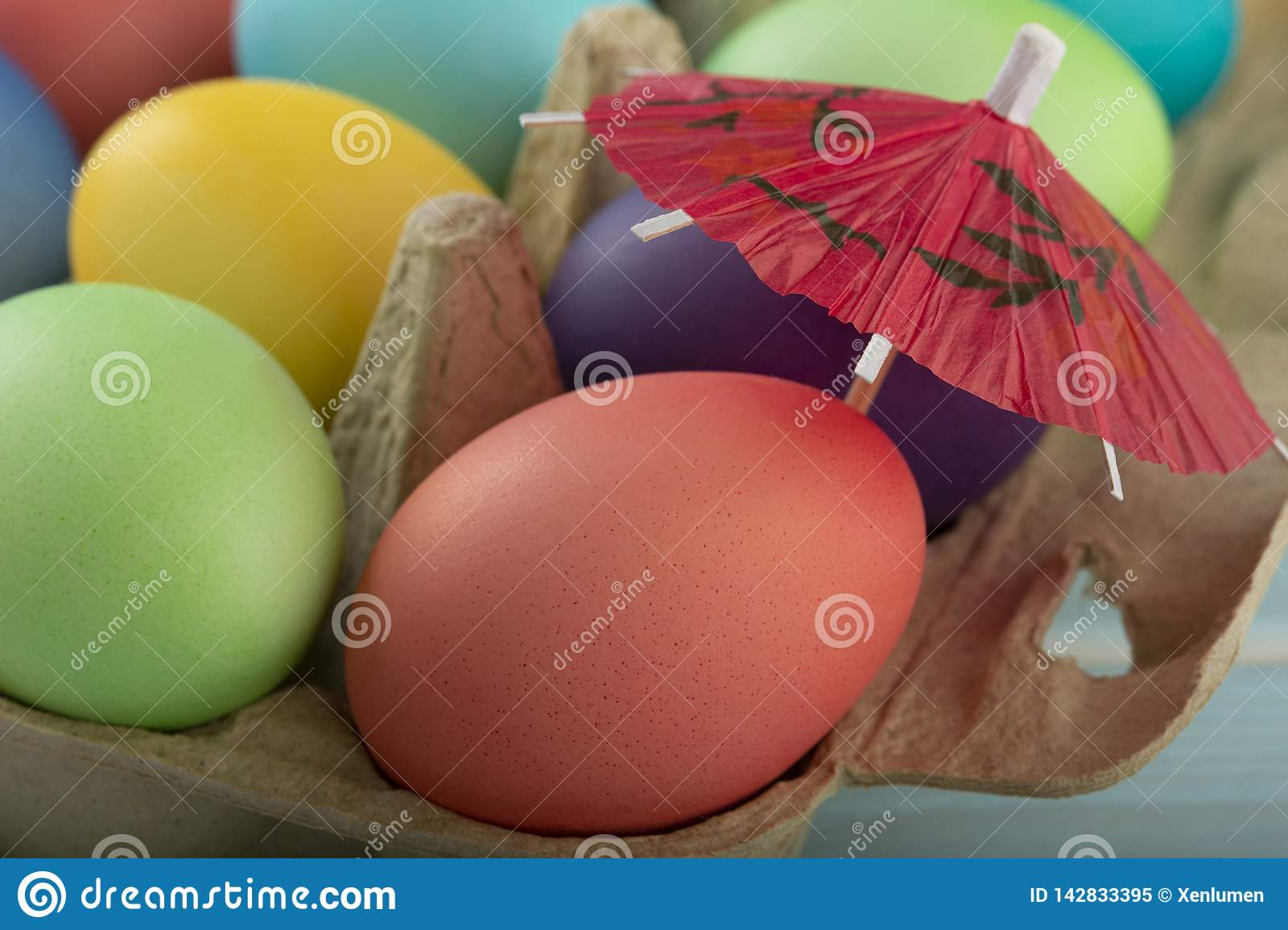 Colorful Easter eggs under umbrella in a box