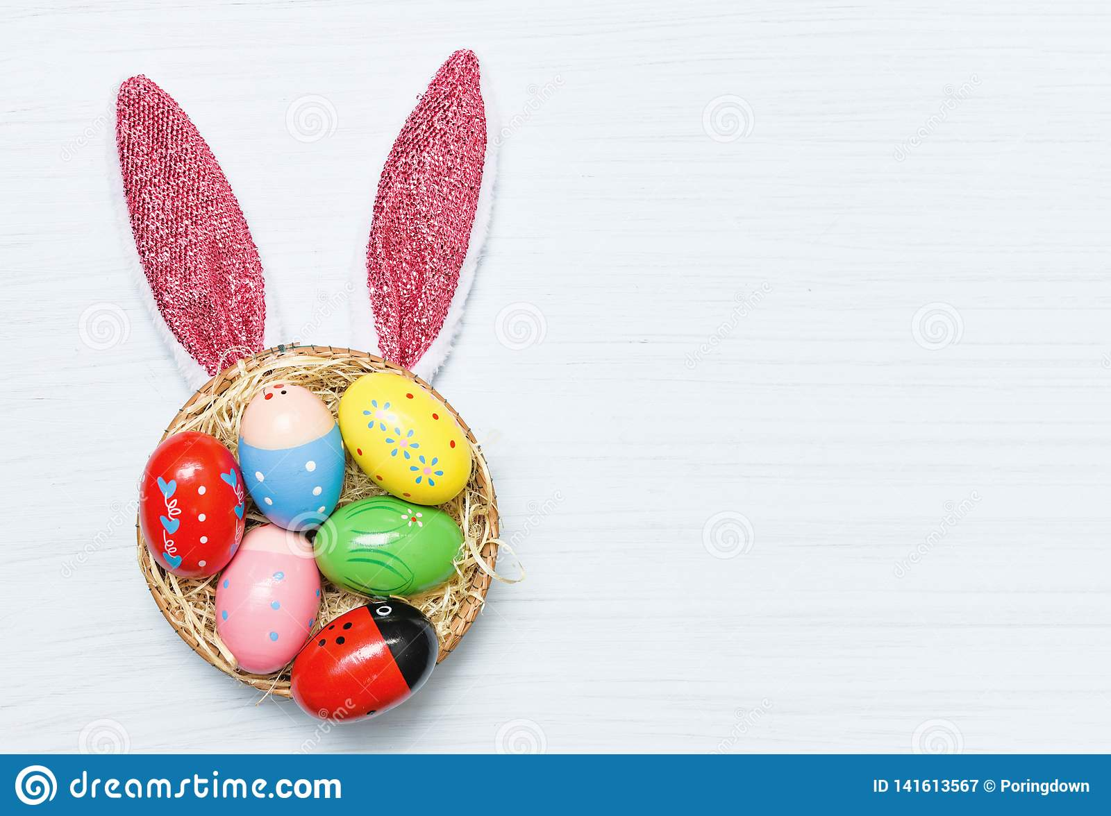 Colorful easter eggs and easter bunny ear rabbit in basket nest