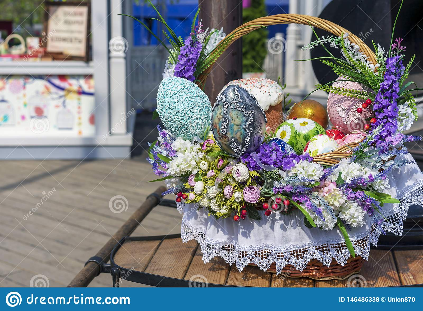 Colorful Easter eggs and Easter cakes in a wicker basket