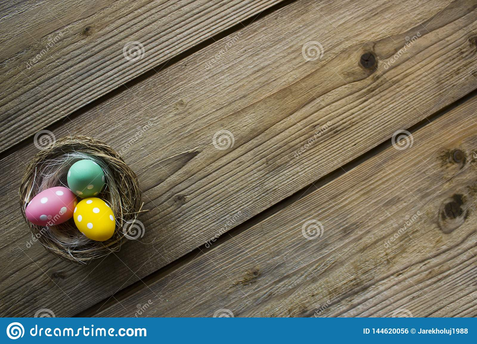 Colorful easter eggs in nest on wooden table