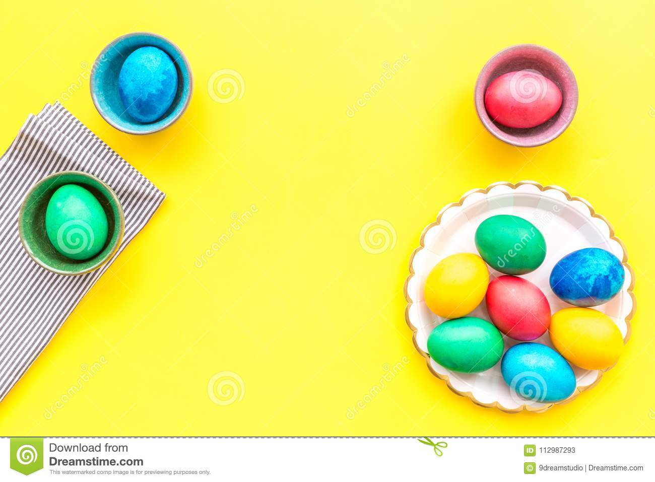 Colorful easter eggs on plate on yellow background top view mock-up