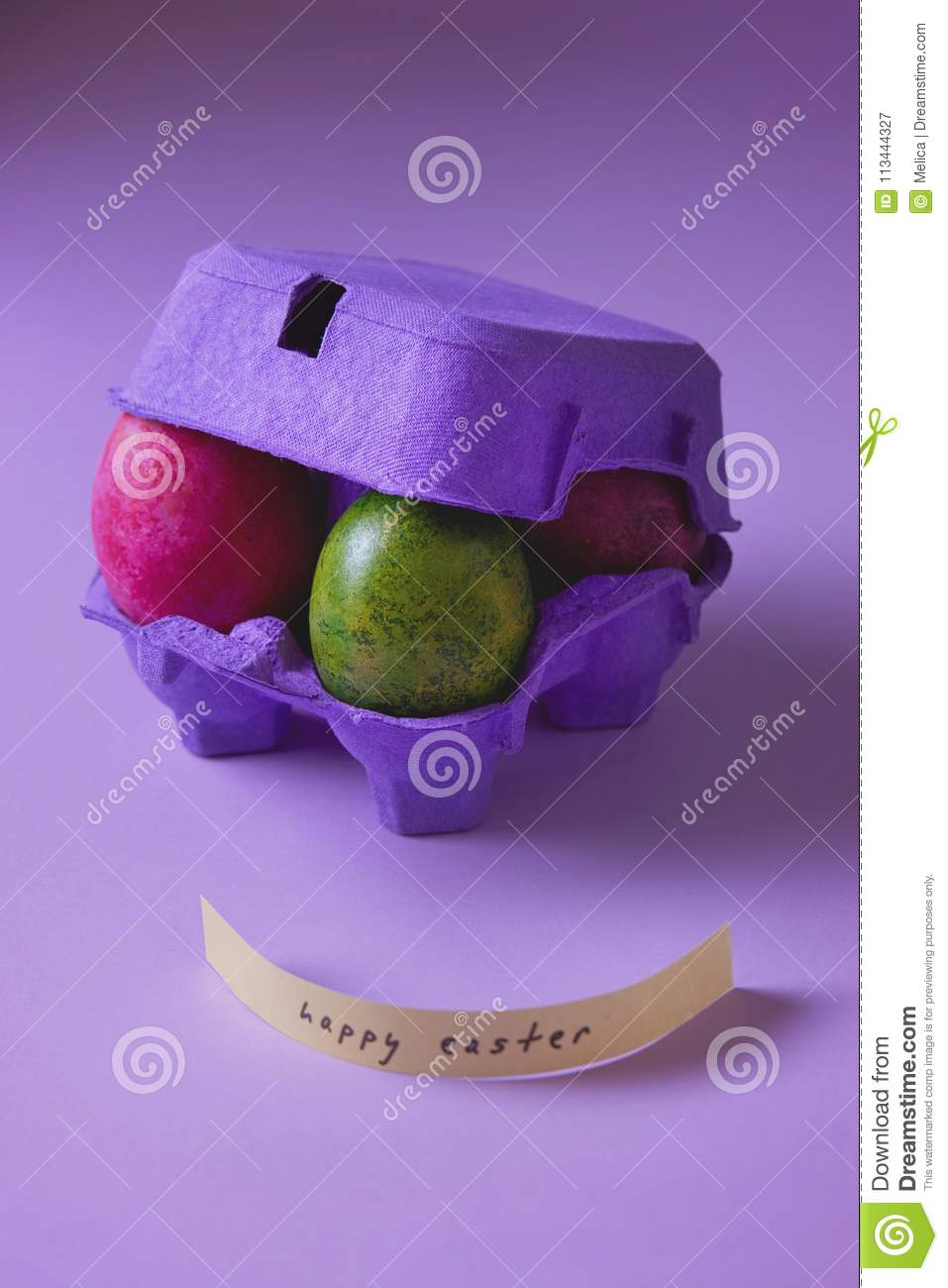 Colorful Easter eggs in purple egg box