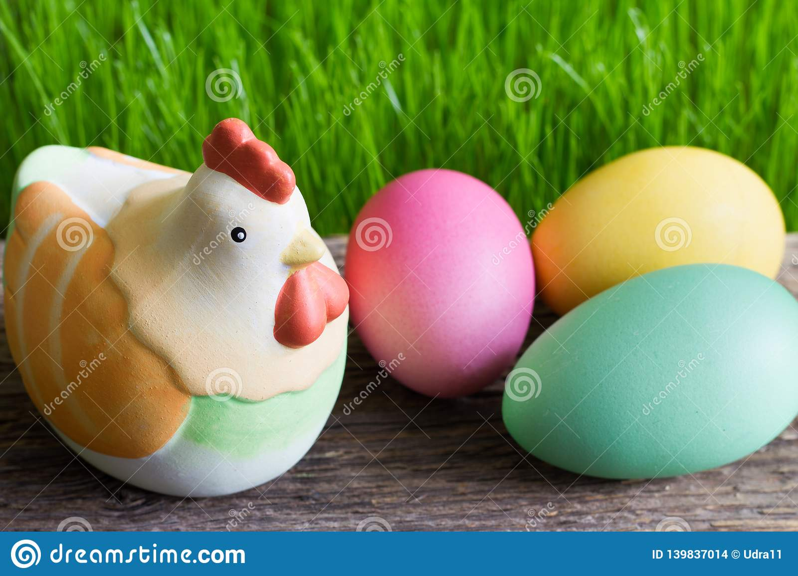 Colorful easter eggs on wooden plank and green grass