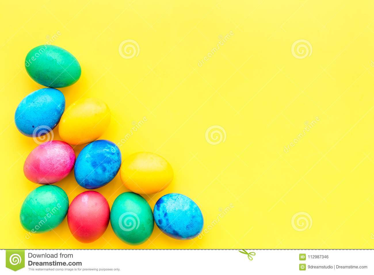 Colorful easter eggs on yellow background top view mock-up