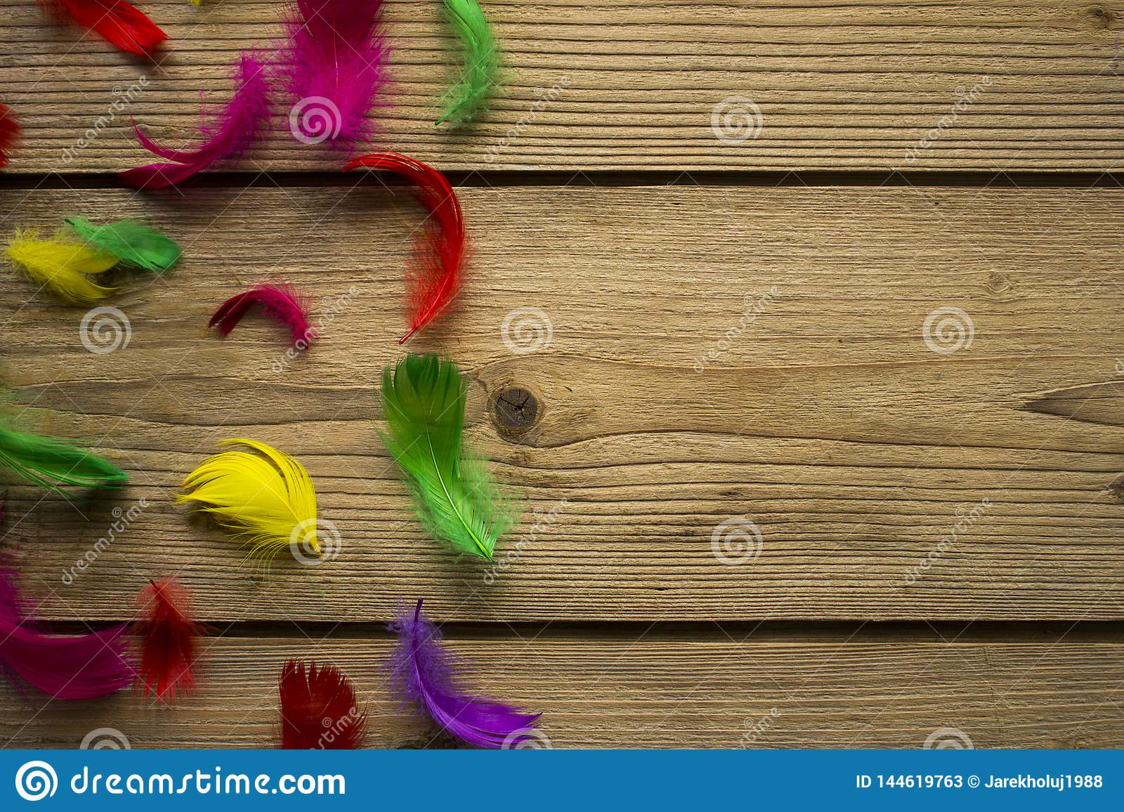 Colorful easter feathers on wooden table