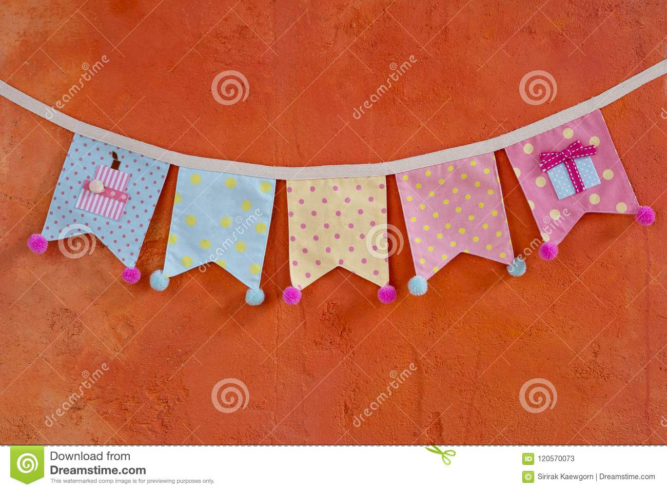 Colorful Fabric Party Flag Design Hanging Over Orange Cement Wall
