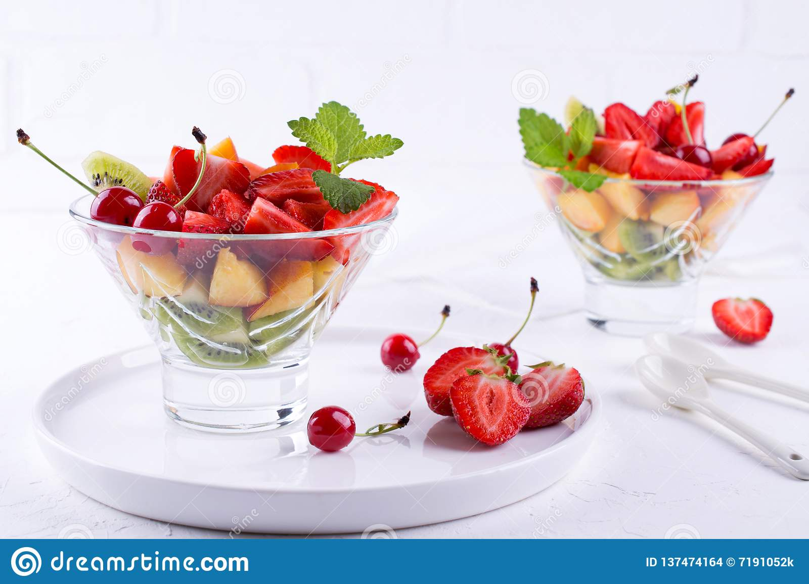 Colorful fruit salad in the glass bowl. Strawberries, kiwis and apricots dessert