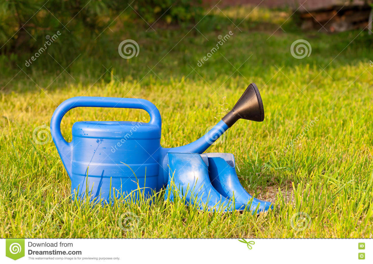 Colorful garden tools watering can rubber boots and rake for Lawn and garden implements