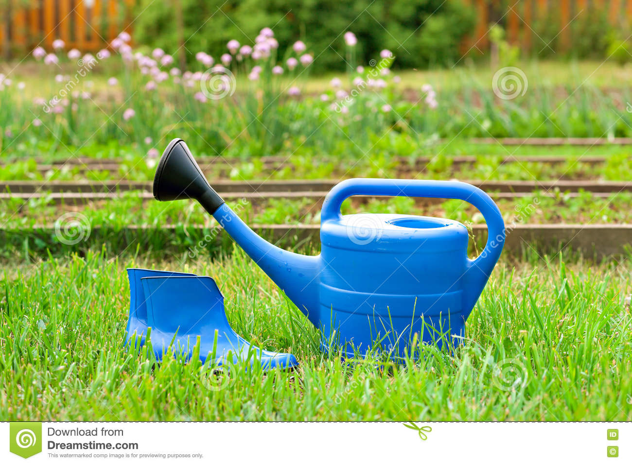 Colorful garden tools watering can rubber boots and rake for Gardening tools watering