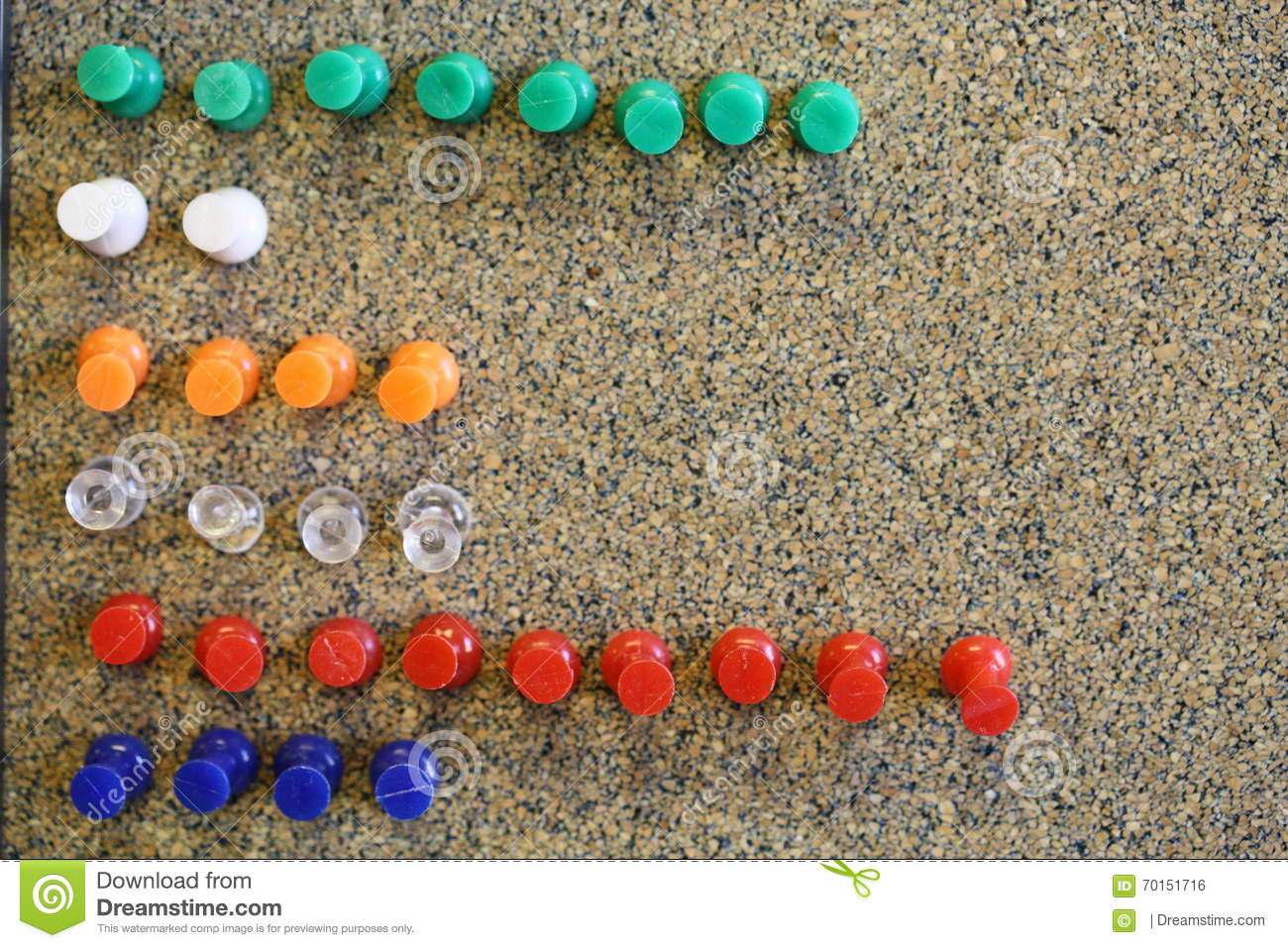 Colorful green white orange clear red blue push pins in bulletin board