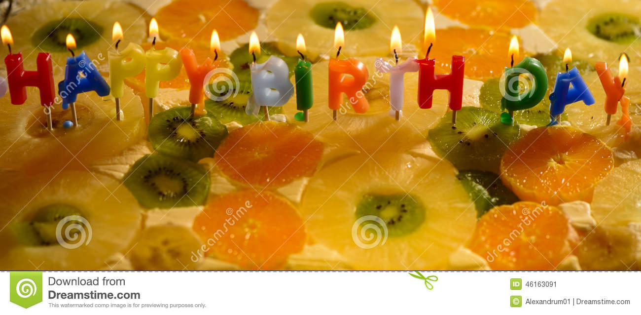 Birthday Greetings From Burning Candles On A Colored Fruit Cake