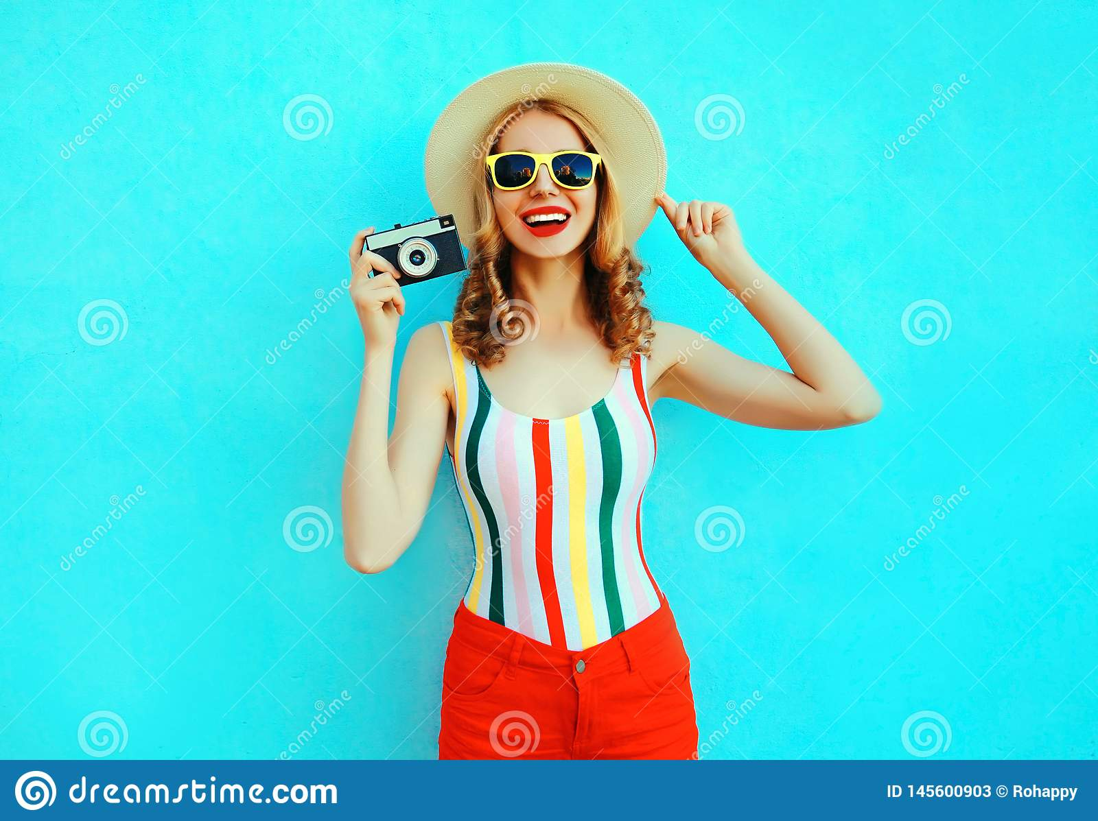 Colorful happy smiling young woman holding retro camera in summer straw hat having fun on blue wall