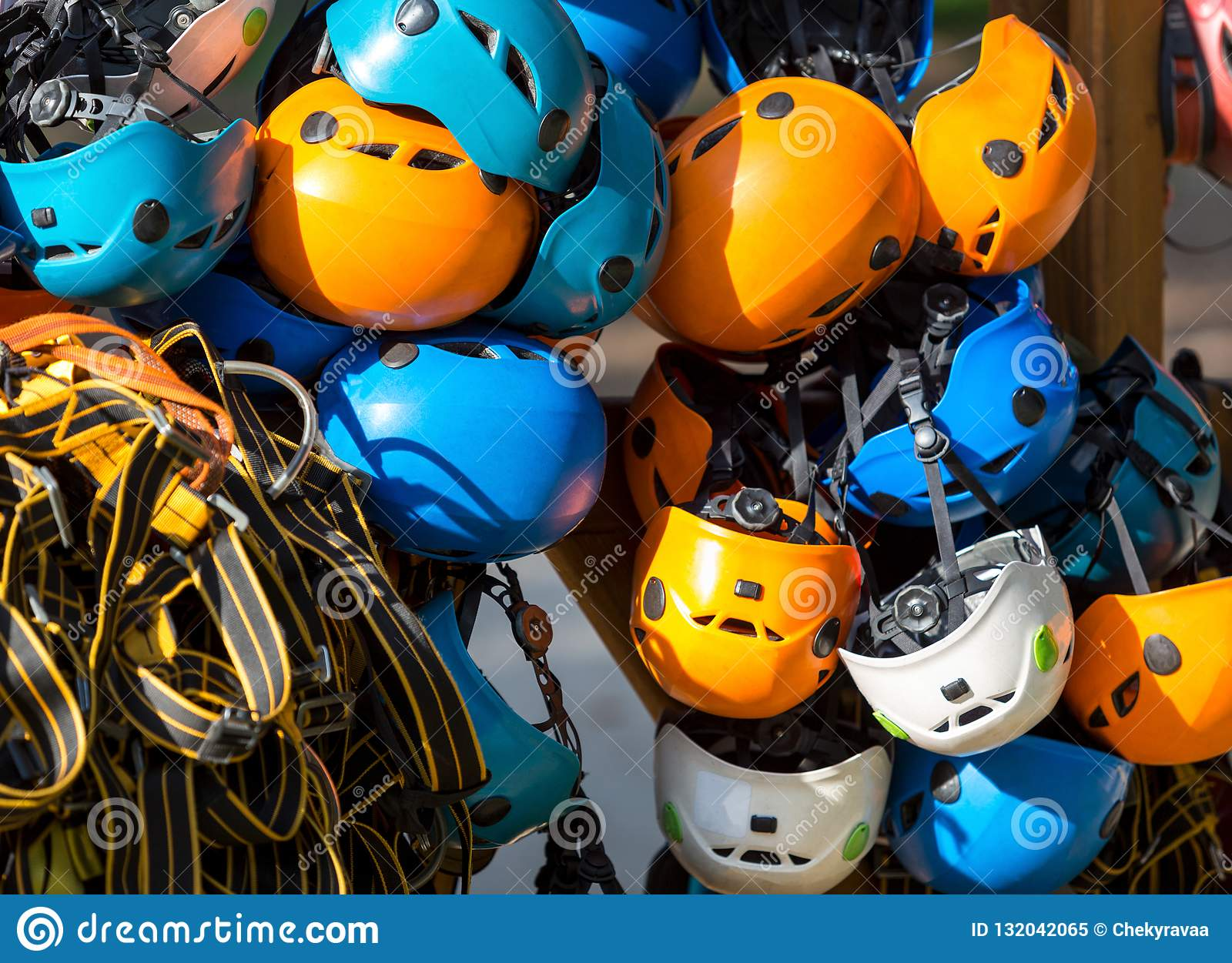 Colorful helmets for kids and adults in the rope park in summer at sunlights. Active sport