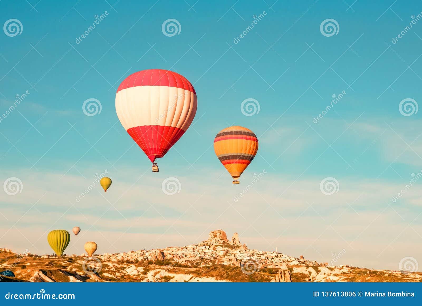 Colorful hot air balloons flying near Uchisar castle at sunrise, Cappadocia, Turkey