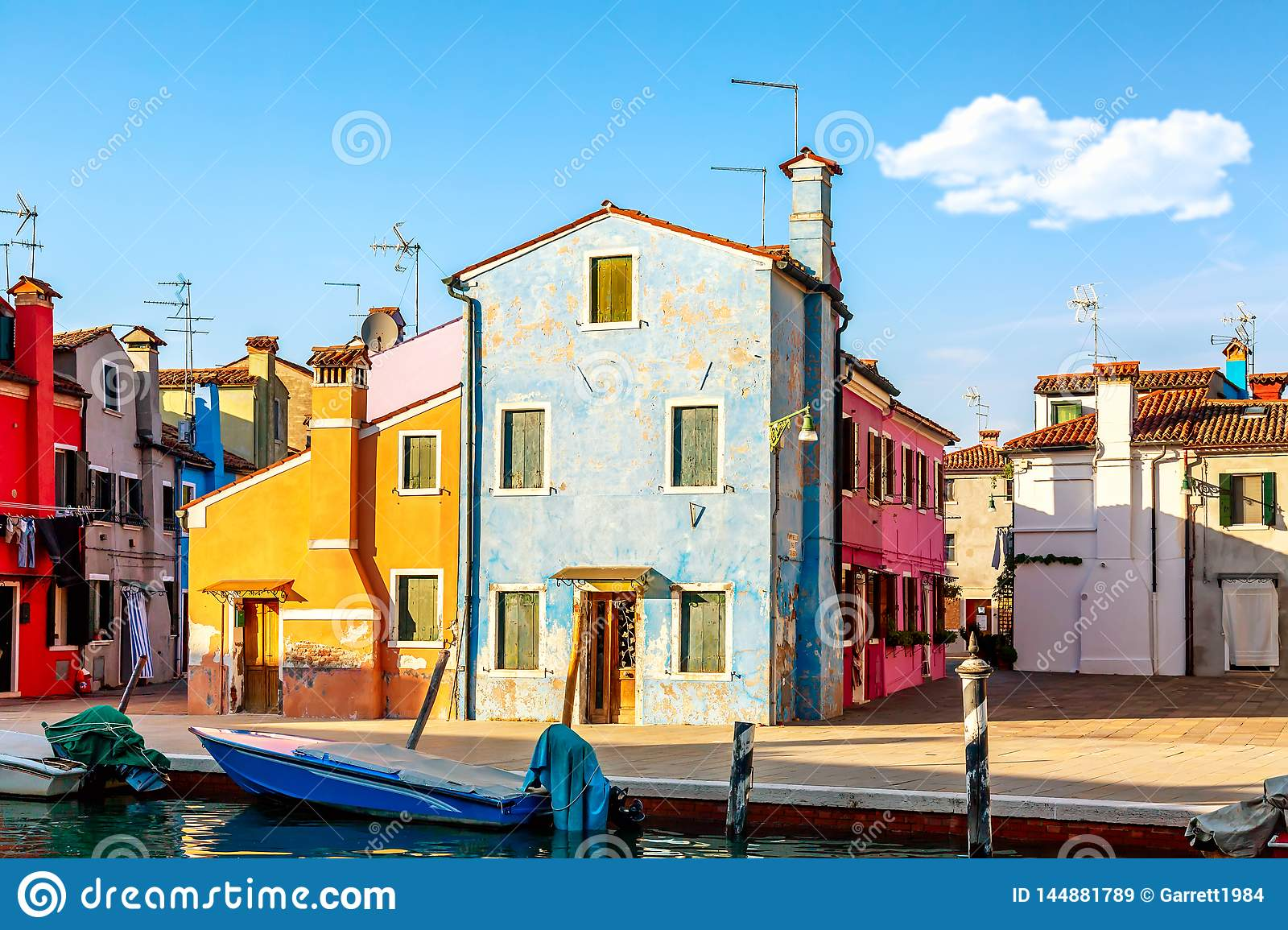 Colorful houses in Burano near Venice, Italy with boats and beautiful blue sky in summer. Famous tourist attraction in Venice