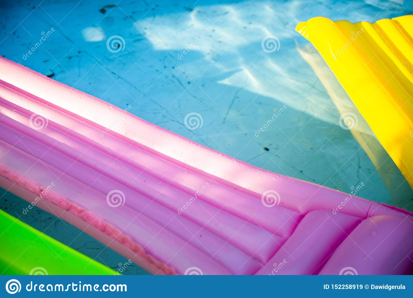 Colorful inflatable mattress in dirty swimming pool. Swimming pool with dirt and leaves on the bottom