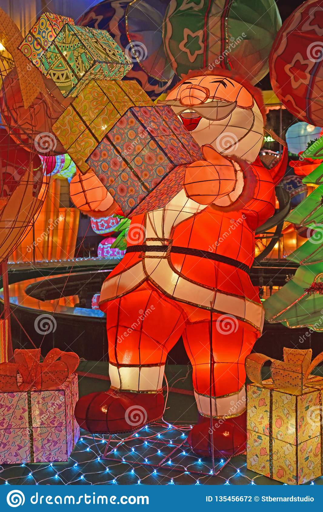 Colorful light decoration of Santa Claus laughing looking happy carrying piles of gift boxes