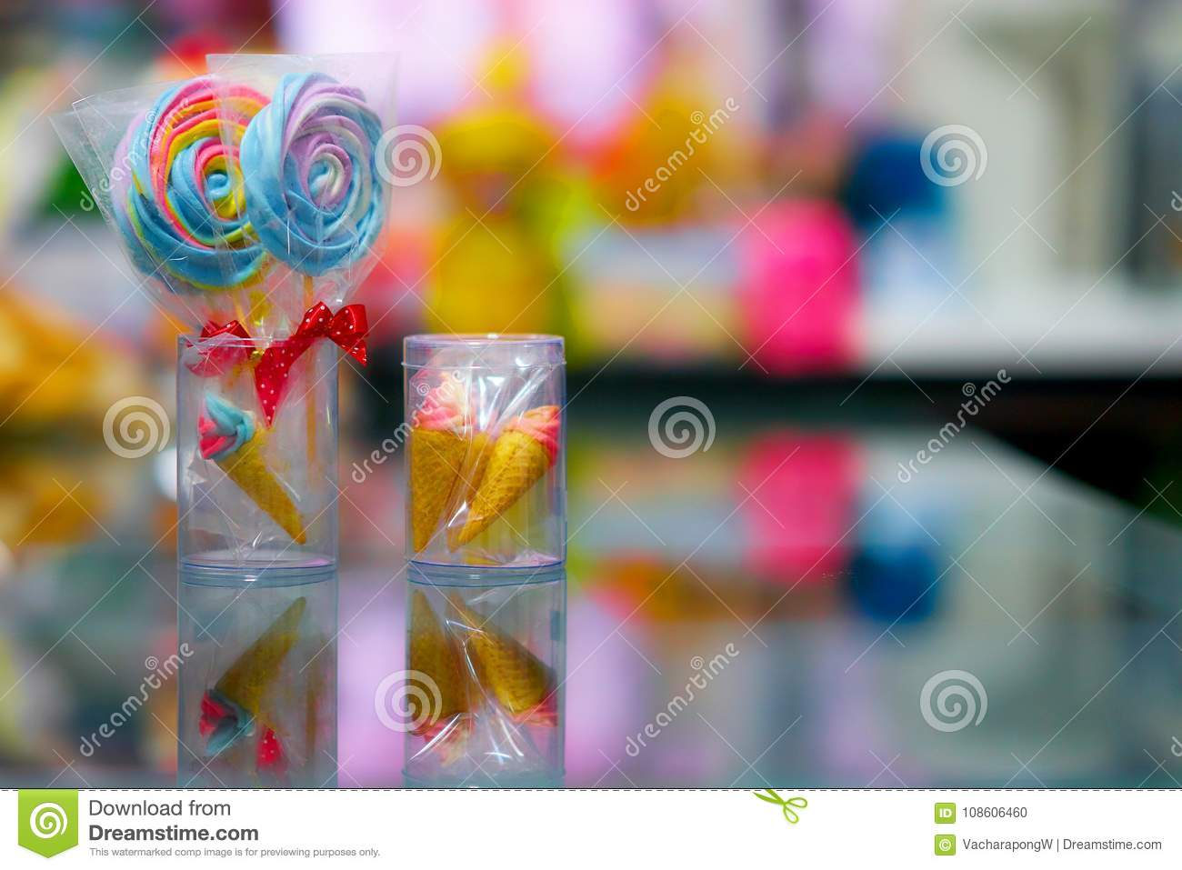 Colorful lolipop and mini cone in plastic box with reflection