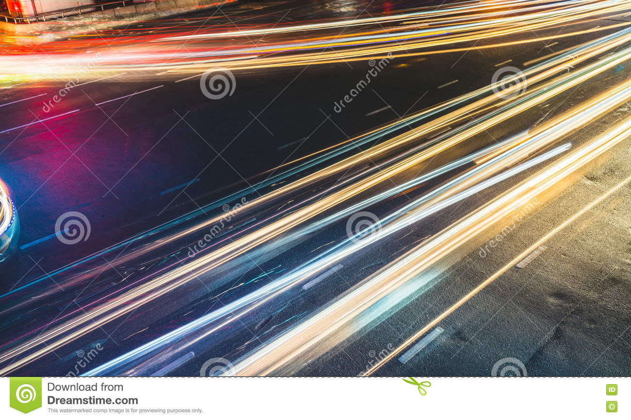 Colorful long exposure light trails across road junction, traffic concept or speed abstract