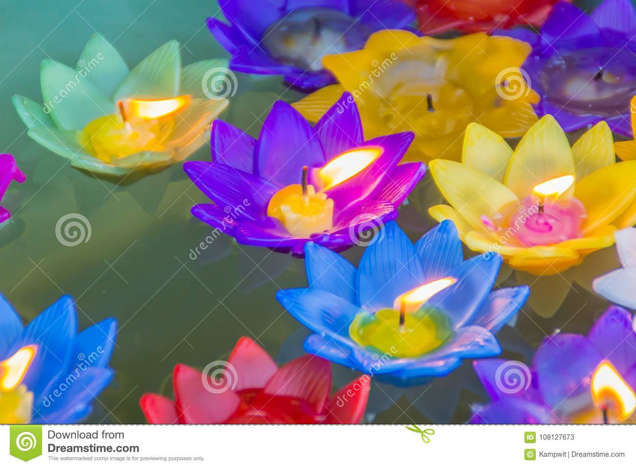 Colorful Lotus Flower With Burning Candles Are Floating On The Water